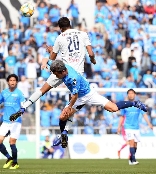 横浜FC・FWカズ(前方)と競り合う福岡DF三国ケネディエブス(2019年4月7日)