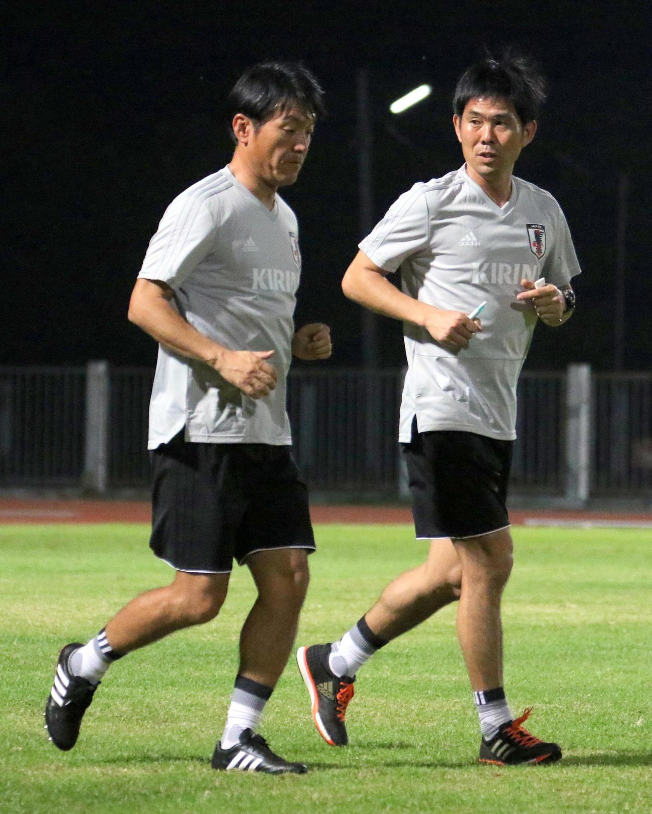17年12月、タイ・ブリラム初練習でU-20日本代表の横内コーチ(左)は森保監督と打ち合わせしながら走る