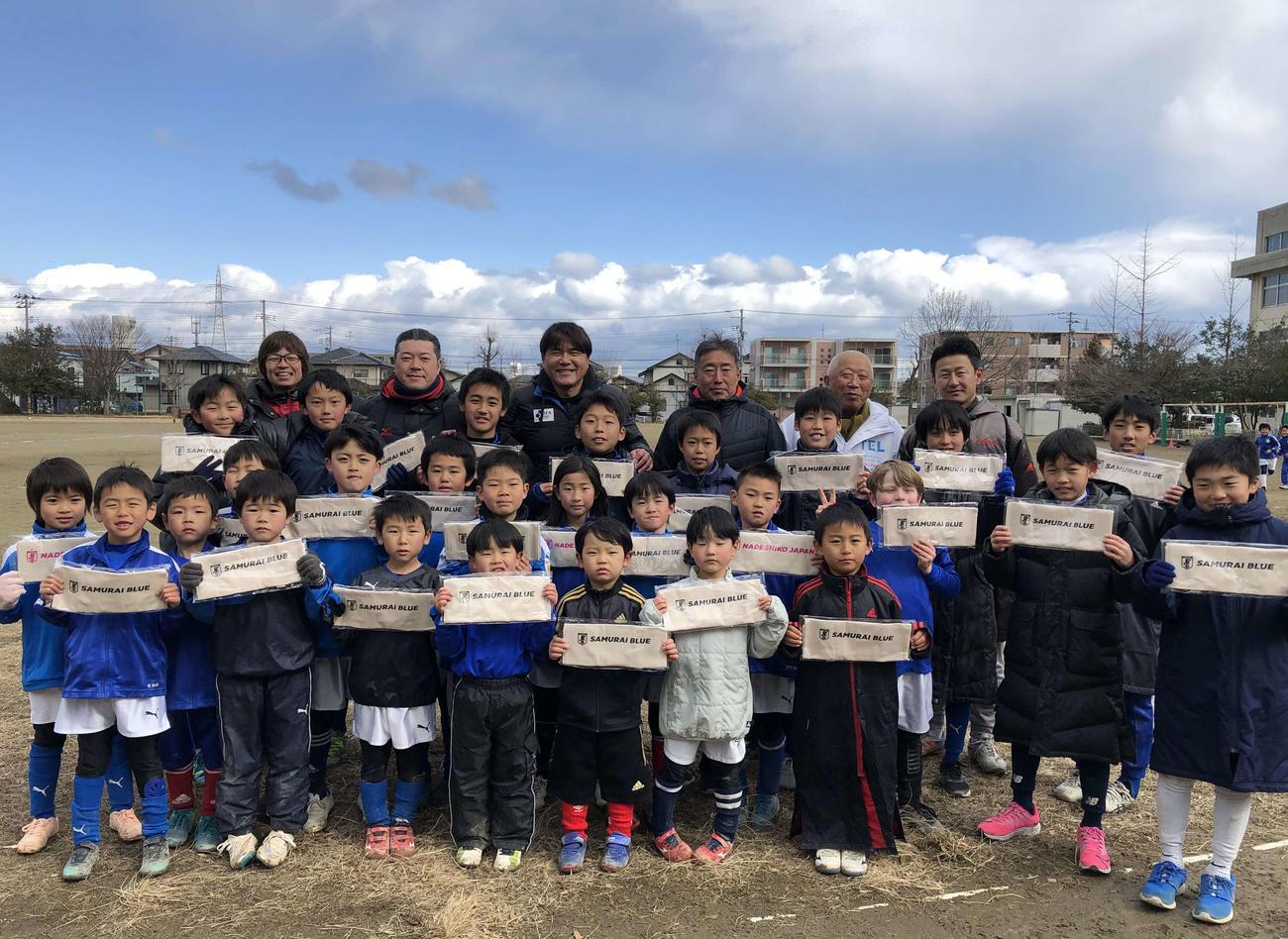 復興支援活動の一環で指導した宮城・高砂SSSの児童たちと記念撮影する手倉森浩氏(最後列左から3人目)(本人提供)