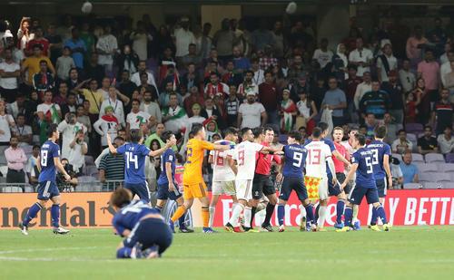 日本対イラン 後半、両チームのイレブンが入り乱れて乱闘騒ぎになる。手前はセンターサークル付近で倒れ込む大迫(撮影・河野匠)