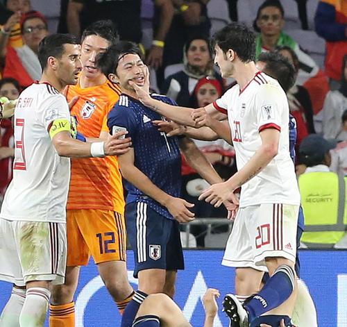 日本対イラン 後半、両チームがもみ合いとなり、柴崎(中央)のアゴをつかむアズムン(右)(撮影・河野匠)
