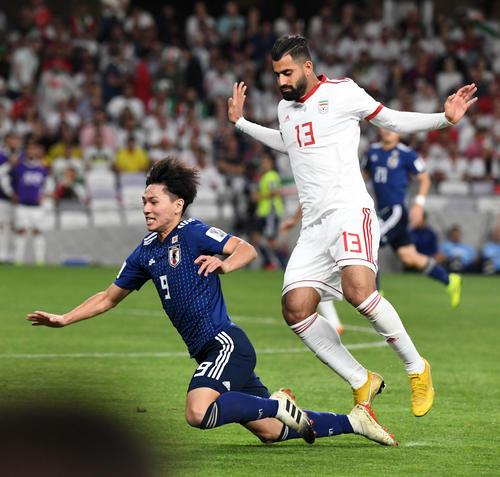 日本対イラン 後半、南野(左)はカナニに倒される(撮影・横山健太)