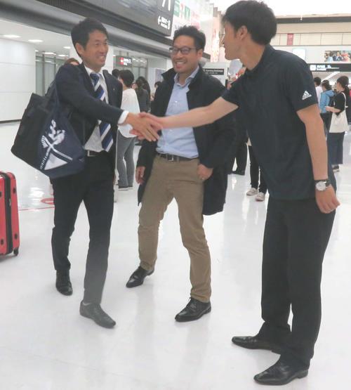 フランス遠征から帰国し、関係者と握手を交わすU-19日本女子代表の池田監督(左端)(撮影・松尾幸之介)