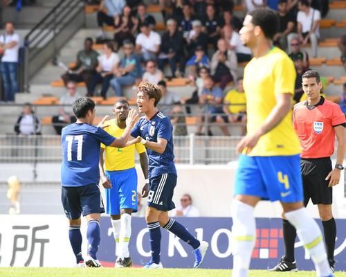 日本対ブラジル 前半、ゴールを決めた小川(中央)は旗手とタッチをかわす(撮影・山崎安昭)