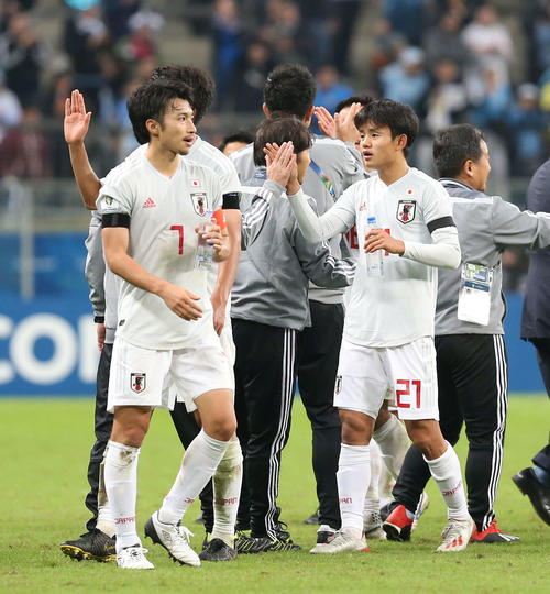 日本対ウルグアイ ウルグアイと引き分け、スタッフ陣とタッチを交わす久保(右)。左は柴崎(撮影・河野匠)