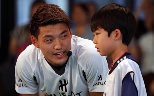 子どもに優しく話しかける日本代表MF堂安(撮影・大野祥一)