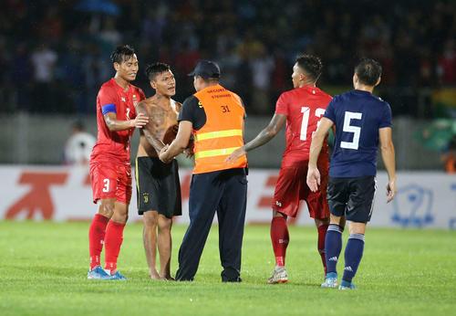 日本対ミャンマー 前半、ピッチに乱入した観客を取り押さえる警備員。右端長友(撮影・河野匠)
