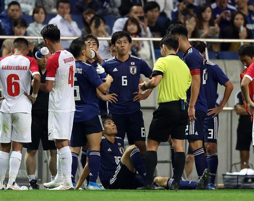 日本対モンゴル 後半、相手と接触し、座り込む冨安(下)(撮影・狩俣裕三)