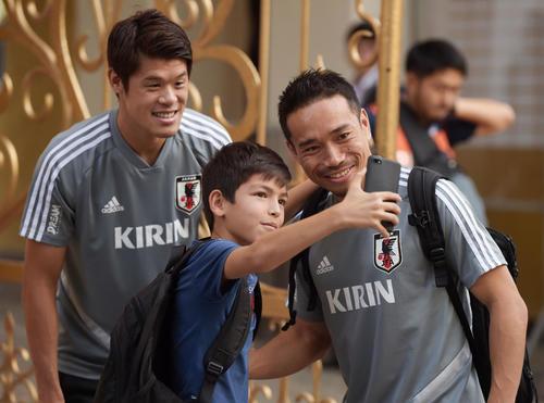 タジキスタンの子供と笑顔で写真に納まる酒井(左)と長友(撮影・横山健太)