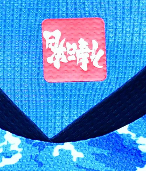 お披露目されたサッカー日本代表2020新ユニホーム。首の付け根部分にはコンセプトの「日本晴れ」、ひっくり返して読むと「侍魂」の文字が浮かび上がるアンビグラムアートが施された(撮影・小沢裕)