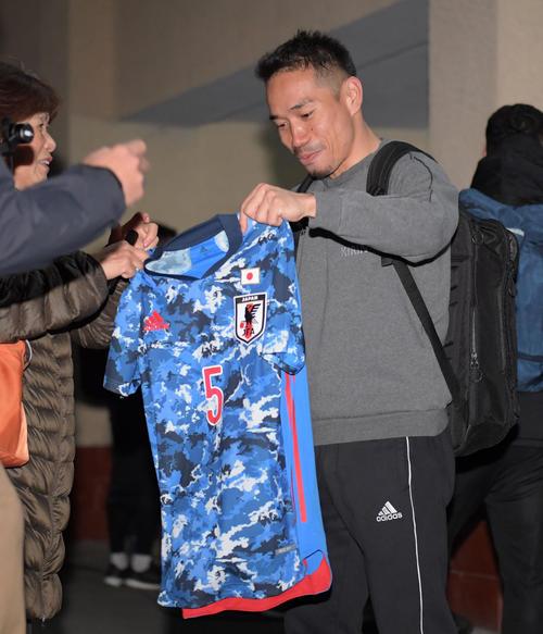 練習後、サポーターの持っていた新ユニホームにサインする長友(撮影・横山健太)