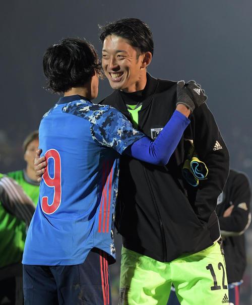 キルギスに勝利し笑顔で抱き合うGK権田(右)と南野(撮影・横山健太)