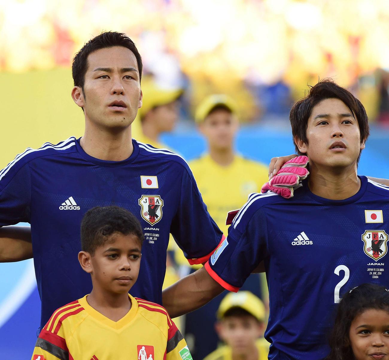 14年6月、W杯ブラジル大会の1次リーグコロンビア戦で、君が代を斉唱する吉田(左)と内田