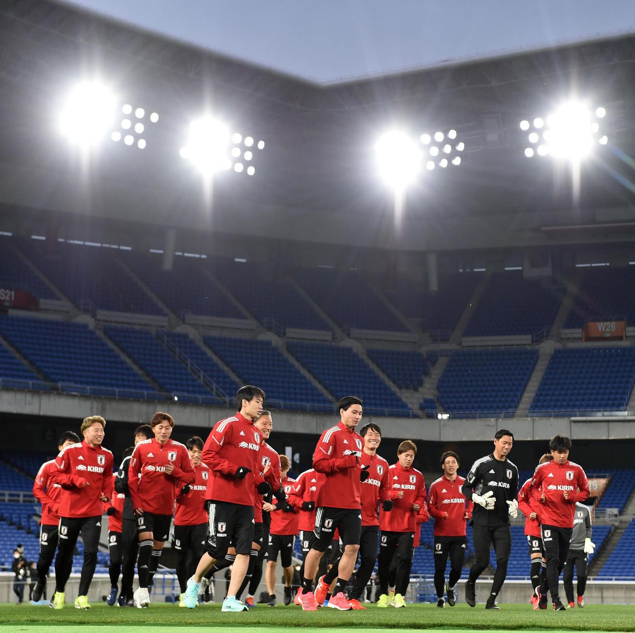 ライトに照らされながらランニングをする日本代表の選手たち(撮影・横山健太)
