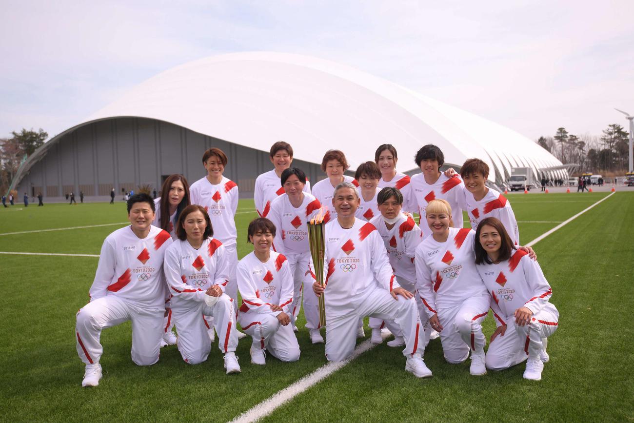聖火リレーを終え、トーチを手にする佐々木則夫氏(前列中央)と2011年サッカー女子W杯で優勝した鮫島(後列左から4人目)ら日本代表「なでしこジャパン」メンバー(代表撮影)=2021年3月25日