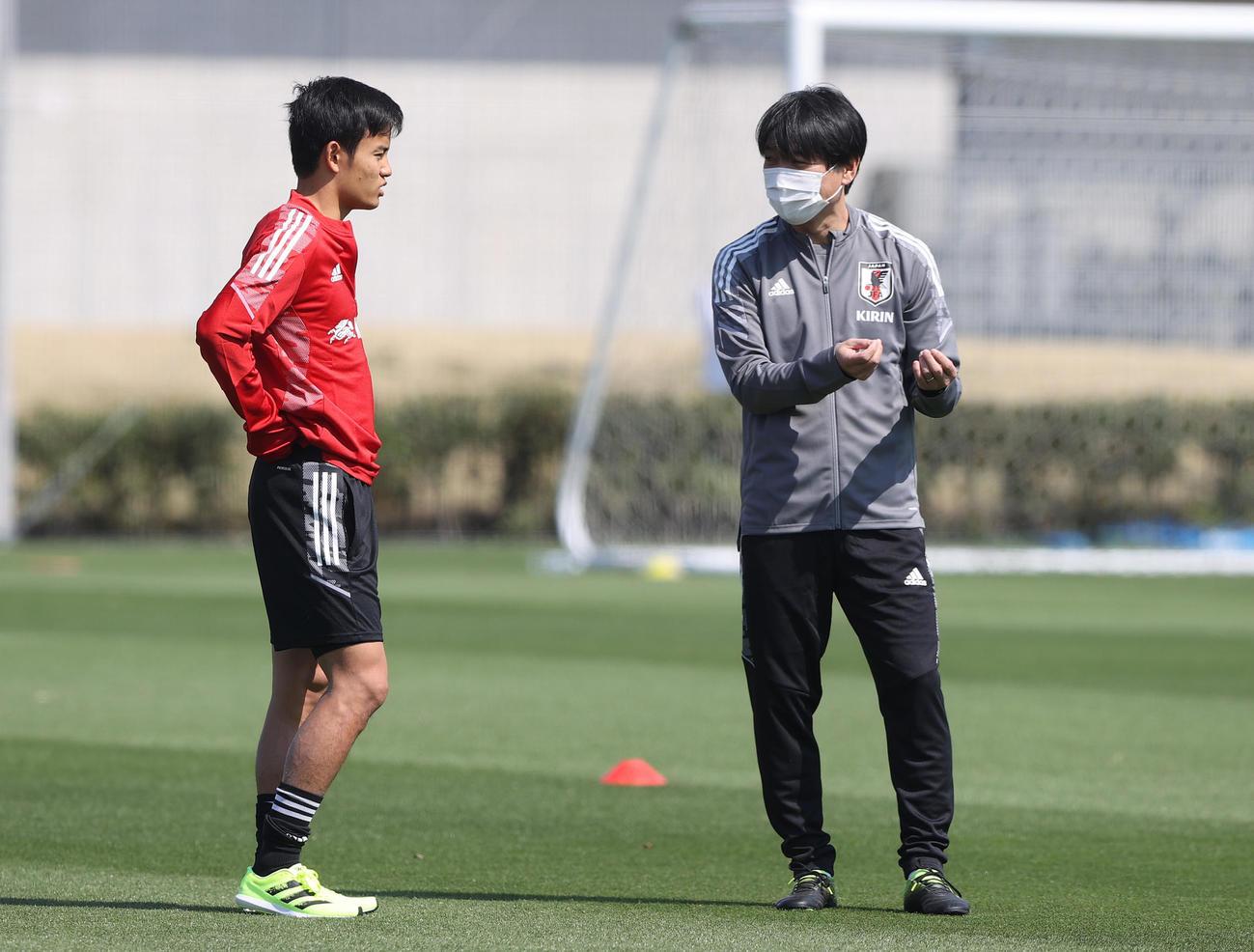 27日の練習中、言葉を交わす久保(左)とU-24日本代表横内監督