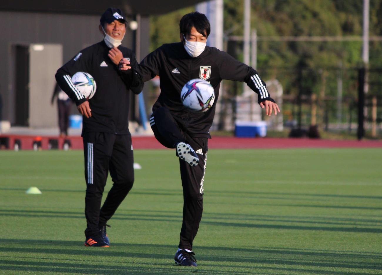 選手とリフティングゲームをする、JFAロールモデルコーチの中村憲剛氏。後ろは森山佳郎監督