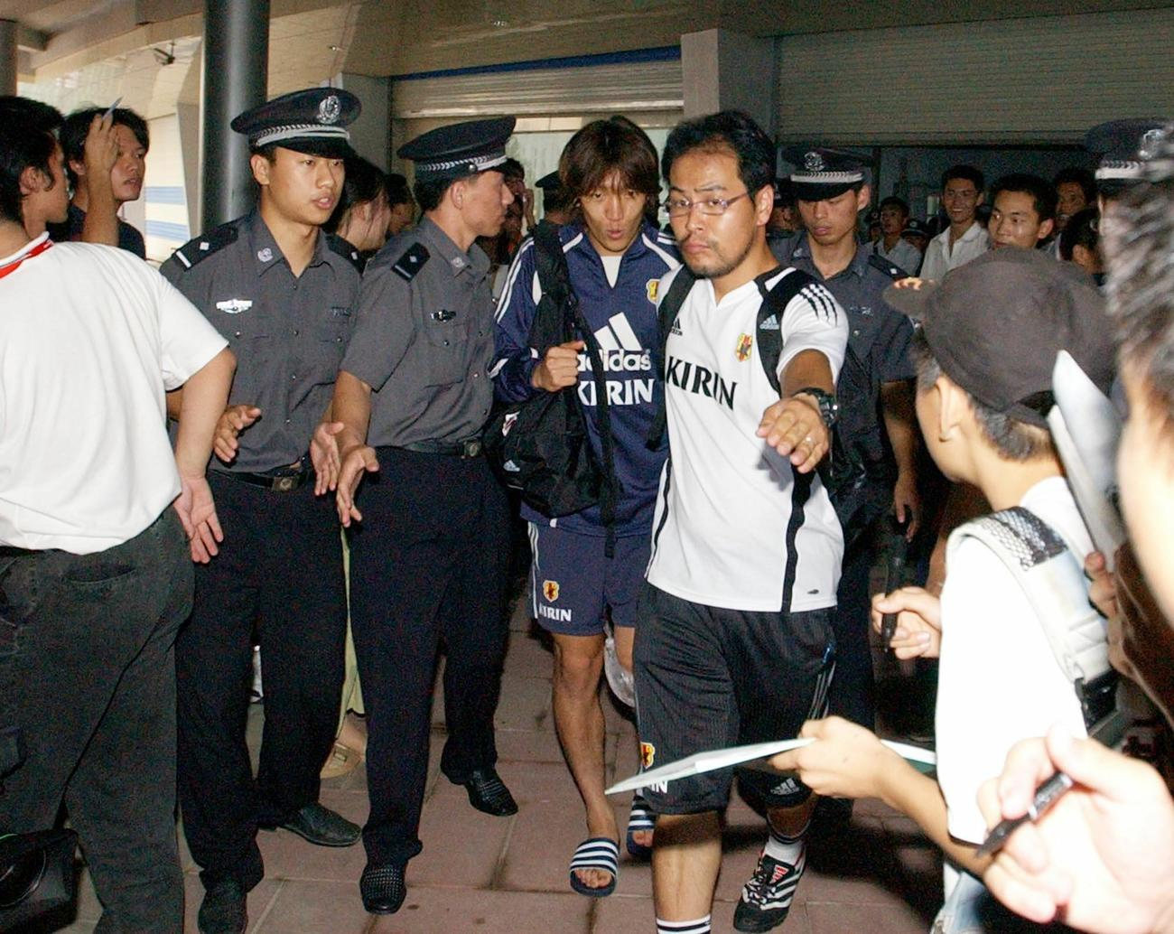 日本代表の練習後、警察官とスタッフに守られながらスタジアムを後にする中村俊輔(2004年8月2日撮影)