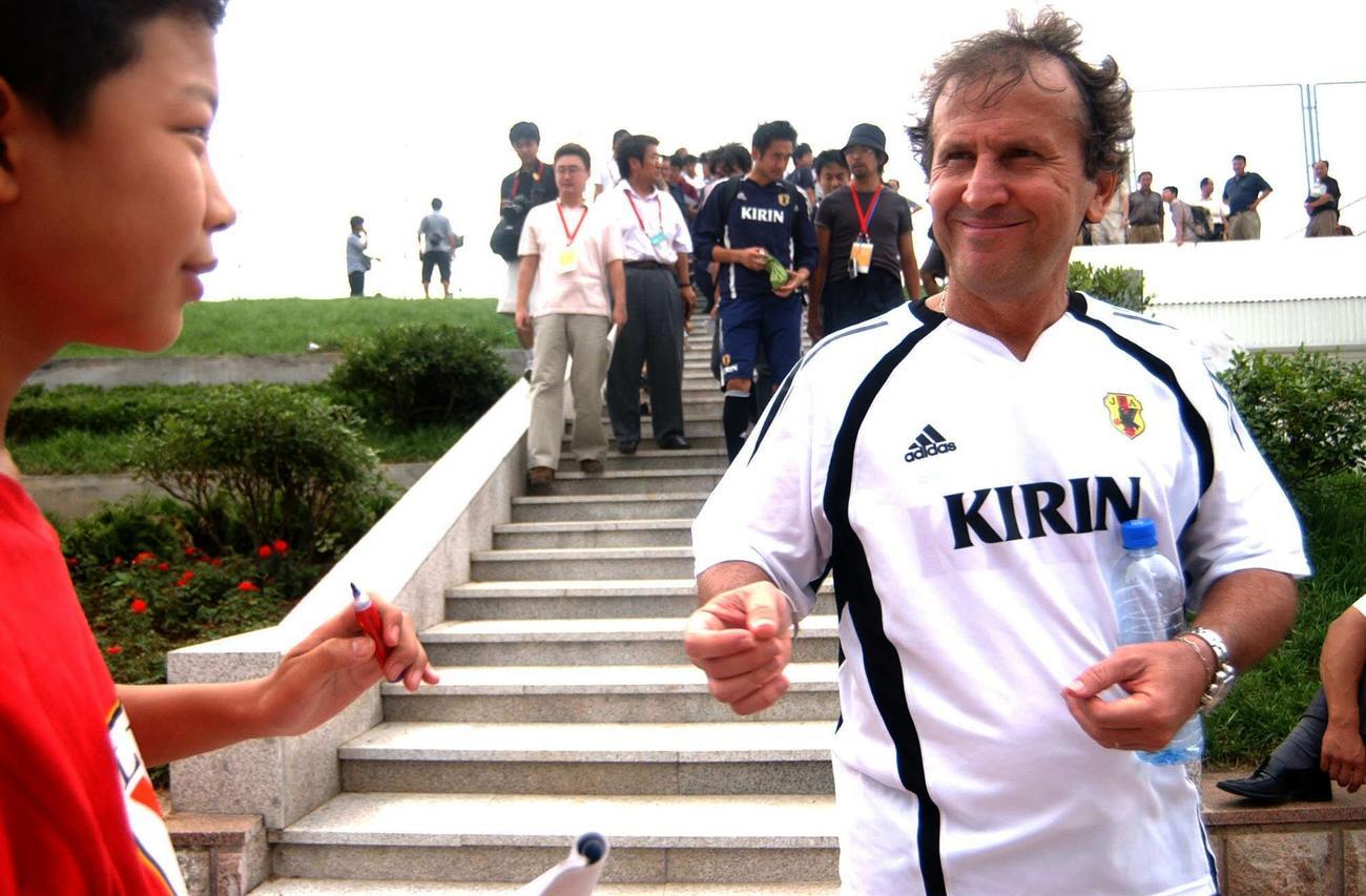 午前練習に参加したジーコ監督は地元の子供のファンに笑顔でサイン(2004年8月4日撮影)
