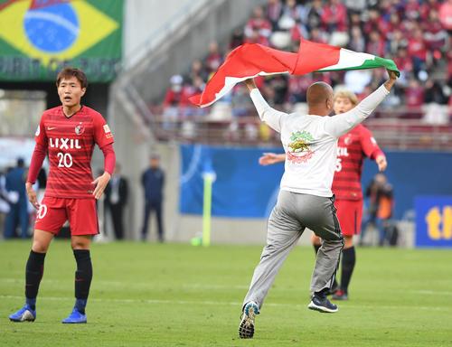 鹿嶋対ペルセポリス 前半、試合中に旗を掲げて走り回る侵入者(撮影・山崎安昭)