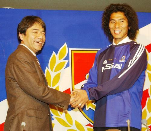 02年2月、横浜に正式に入団を発表した中沢は(右)は左伴繁雄社長とガッチリと握手
