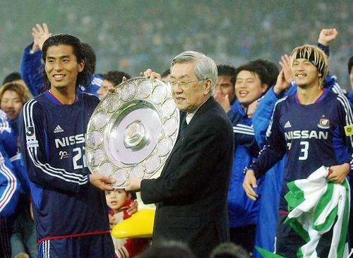 03年11月、鈴木チェアマン(右)から優勝プレートを受け笑顔を見せる中沢。右奥は松田直樹