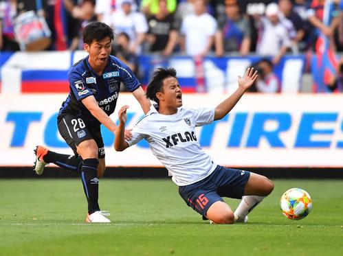 G大阪対東京 前半、G大阪MF高(左)に倒される東京MF久保(撮影・上田博志)