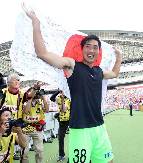 浦和対広島 試合後、サポーターのメッセージが書かれた日の丸を掲げ、笑顔を見せる広島GK大迫(撮影・狩俣裕三)