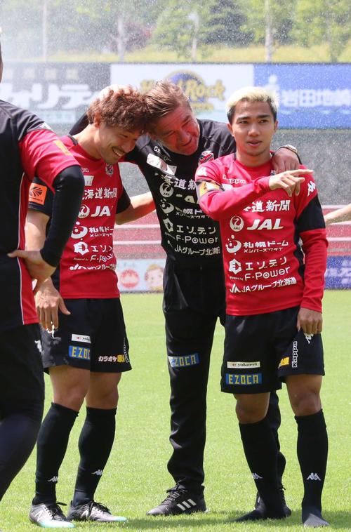 全体練習に合流した札幌MFチャナティップ(右)はペトロビッチ監督(中央)から抱き寄せられる。左はMF白井(撮影・保坂果那)