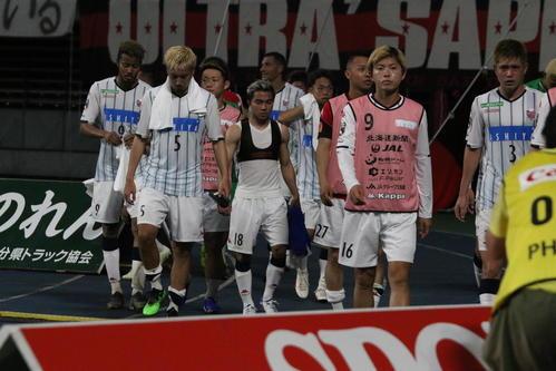 試合に敗れ、悔しそうな表情でグラウンドを後にする札幌イレブン。手前中央はMFチャナティップ(撮影・保坂果那)