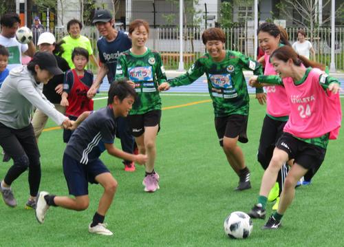 親子サッカー体験教室の手つなぎサッカーで小学生とボールを奪いあう日テレの選手と澤穂希さん(右から2人目)(撮影・松尾幸之介)