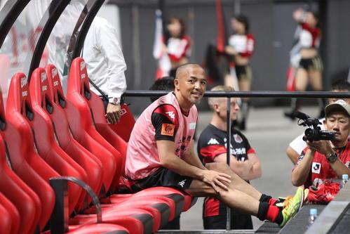 札幌対浦和 試合前、ベンチに座り笑顔を見せる札幌MF小野(撮影・西塚祐司)