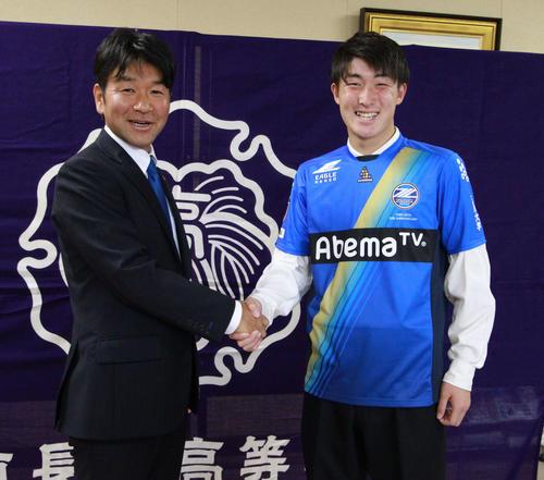 J2町田の丸山強化部長(左)と握手を交わし晴山は笑顔を見せる(撮影・涌井幹雄)