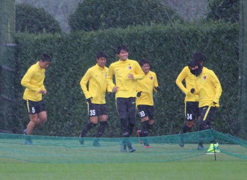 暴風雨の中、顔をしかめながら練習をする選手たち