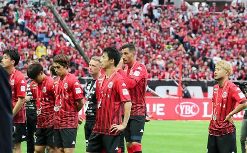 優勝を決めた川崎Fの表彰を悔しそうに見つめる札幌の選手たち(撮影・垰建太)