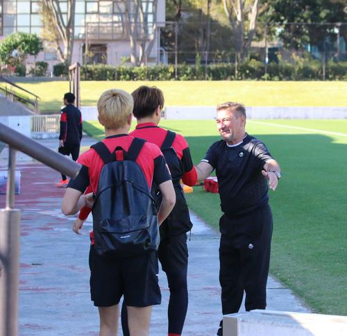 練習場に到着した選手を笑顔で出迎える札幌ペトロビッチ監督(右)(撮影・保坂果那)