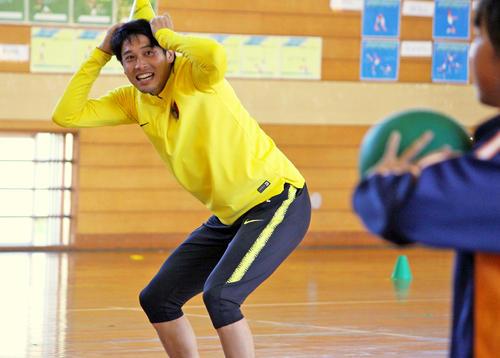 小学生とのドッジボールで、頭にコーンを被って逃げるDF内田篤人(撮影・杉山理紗)