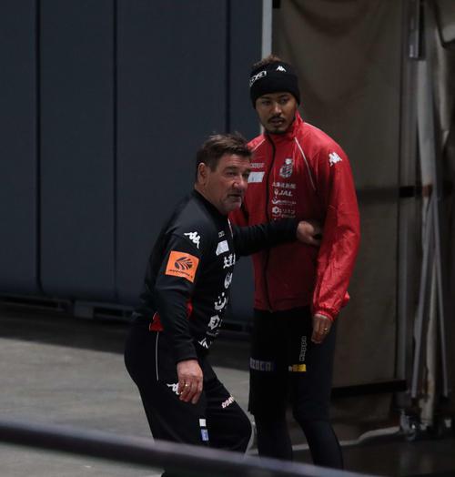 札幌ペトロビッチ監督(左)はFW鈴木に動きを指導しながらピッチに登場する(撮影・保坂果那)