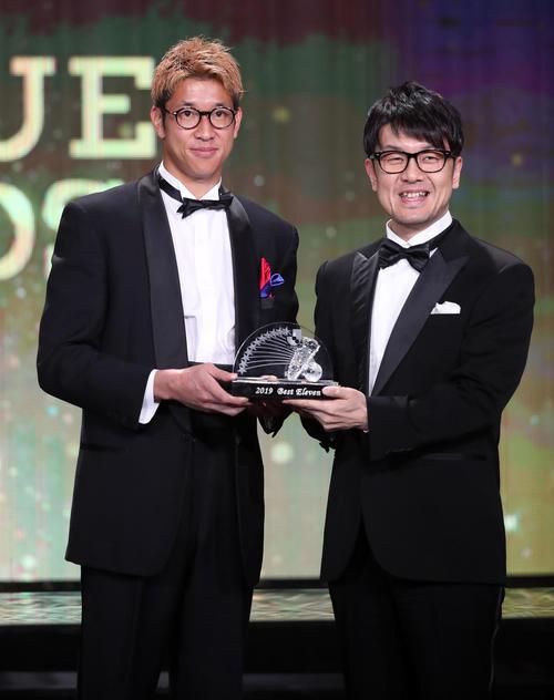 Jリーグアウォーズベストイレブンに選出された東京GK林(左)はプレゼンターの土田晃之と笑顔で写真に納まる(撮影・垰建太)