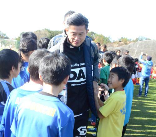 サッカースクールに参加した小学生たちとハイタッチをする横浜FCのFWカズ