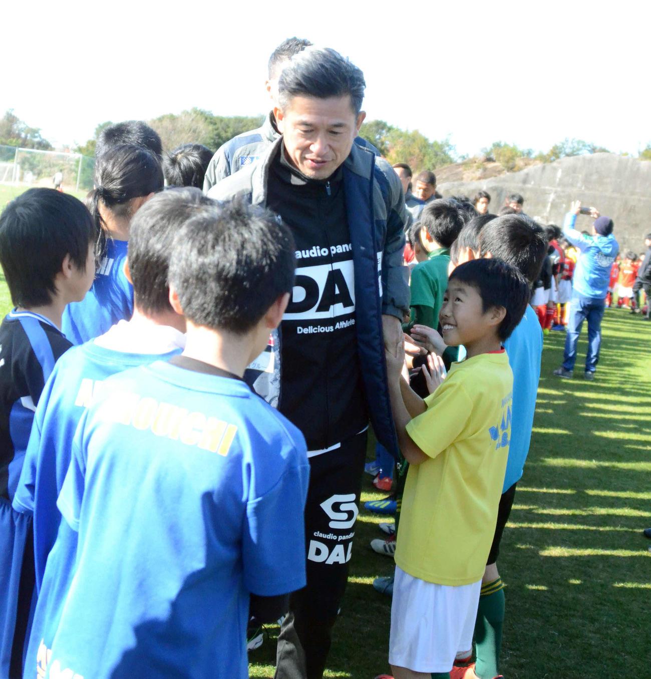 サッカースクールに参加した小学生たちとタッチをする横浜FC・FWカズ