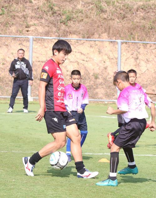 子どもたちを指導する札幌MF金子(左)(撮影・西塚祐司)