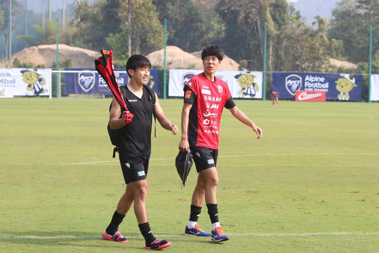 MF金子(左)とグラウンドを引き揚げる札幌DF田中(右)(撮影・西塚祐司)