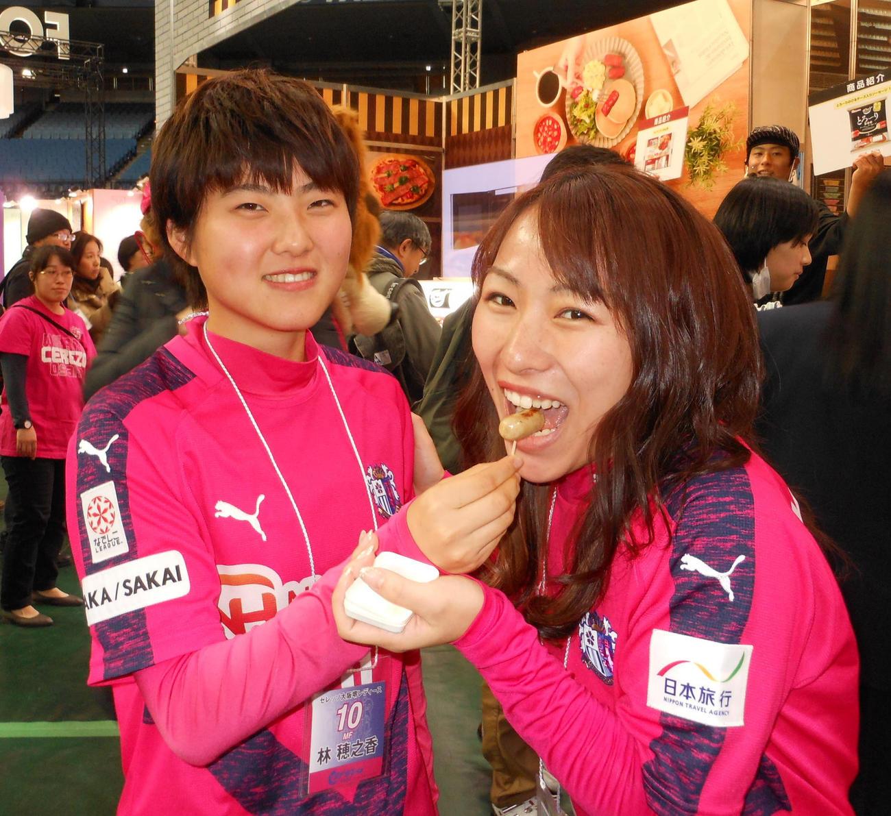 C大阪堺のMF林穂之香(左)は試食会で同僚のMF古沢留衣にウインナーを食べさせる