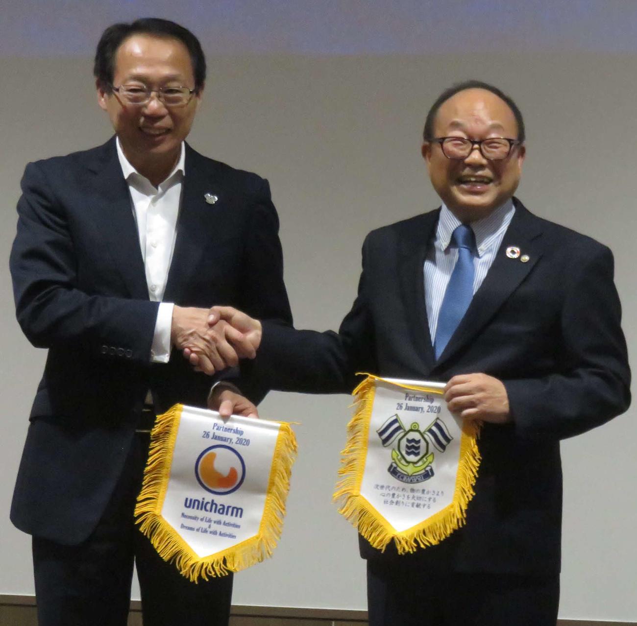 FC今治のシーズン方針発表会で今季のトップパートナーとなったユニ・チャームの石川副社長(右)とフラッグを交換する岡田オーナー