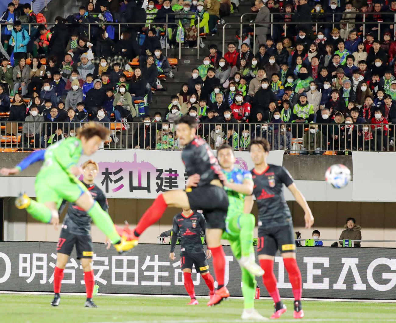 前半、今季初ゴールを決める湘南FW石原直(左)を見届けるマスクを着けたサポーターたち(撮影・河田真司)