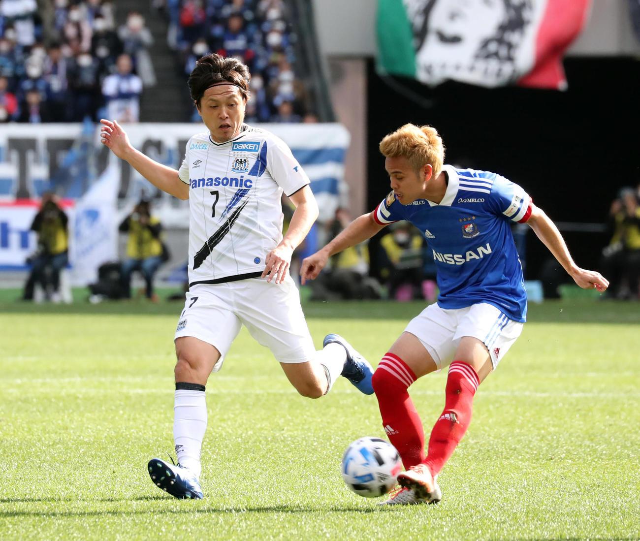 横浜対G大阪 前半、先発出場を果たしJ1通算最多出場記録に並んだG大阪MF遠藤(左)は相手に激しくプレスをかける(撮影・垰建太)