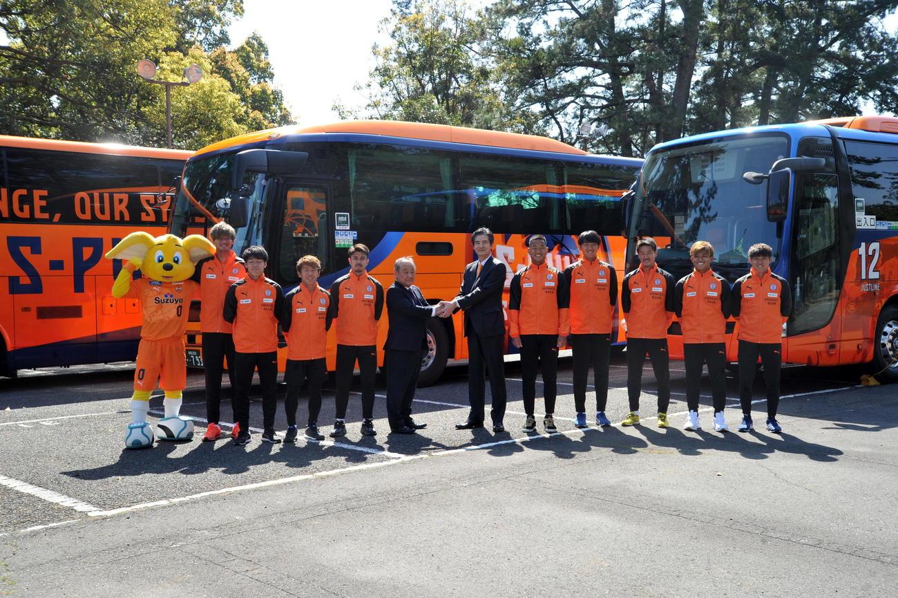 デザインをリニューアルしたバスの前で記念撮影に納まる出席者たち
