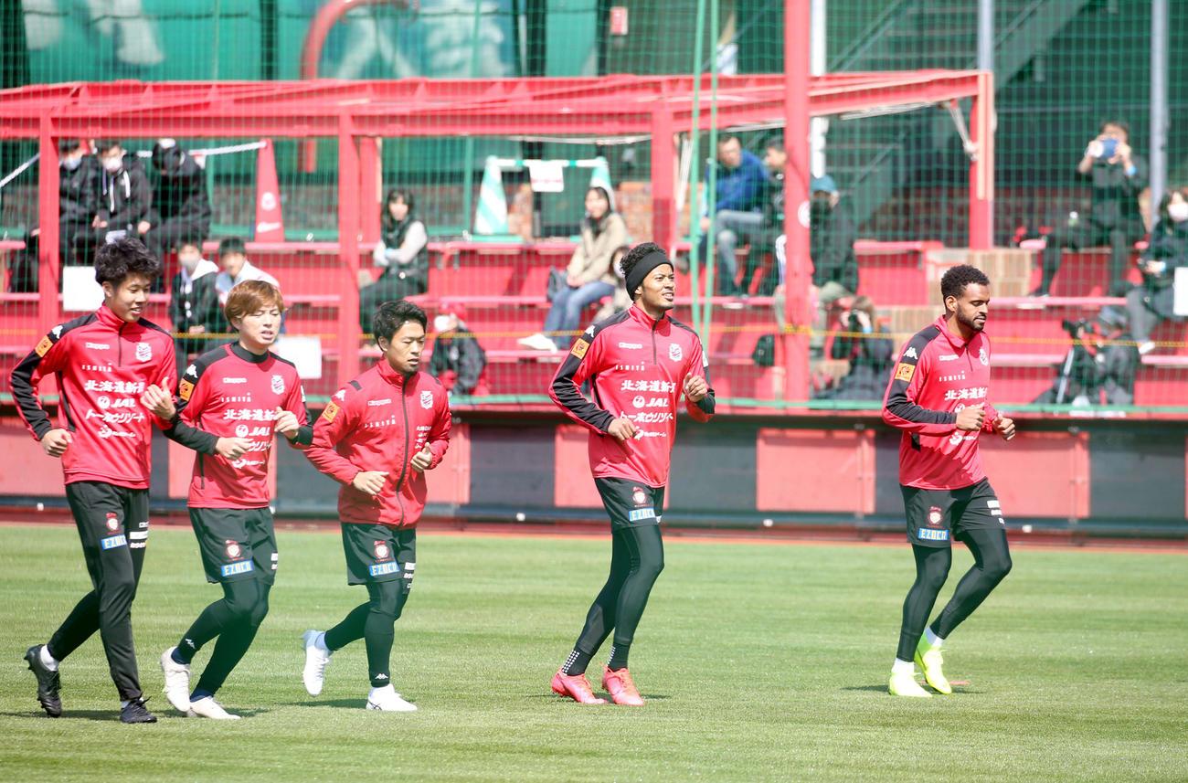 全体練習再開で集まったサポーターの前でランニングをする札幌イレブン。中央はFW鈴木(撮影・佐藤翔太)