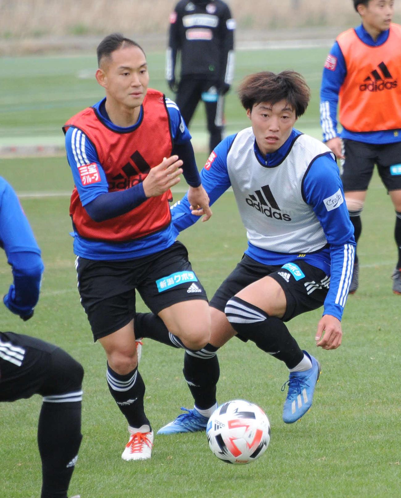 ミニゲームで早川(左)からボールを奪いに行く岡本